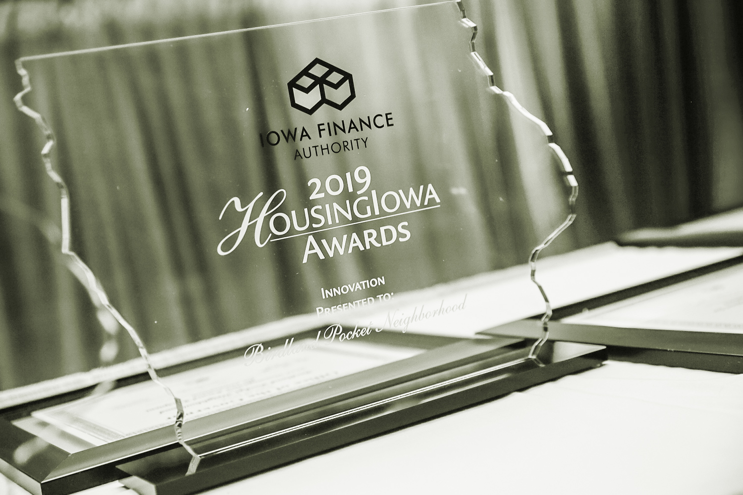 Photo showing an award with Iowa Finance Authority's logo on it. The award is made of glass and is cut in the shape of Iowa.